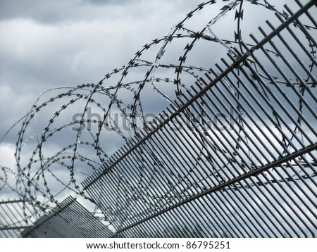 "detail of a safety fence near a racetrack in Southern Germany named ""Hockenheimring"" in dramatic clouded ambiance - stock photo"