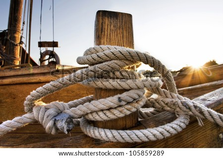 detail of a sailing boat, marine white rope, Rope on an old sailboat - stock photo