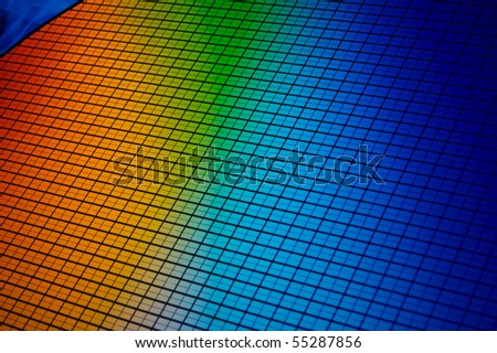 detail of a silicon chip wafer reflecting different colors - stock photo