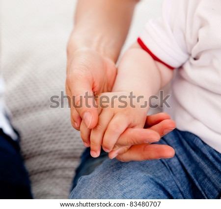 Detail of a small toddler boy holding his mothers hand - stock photo