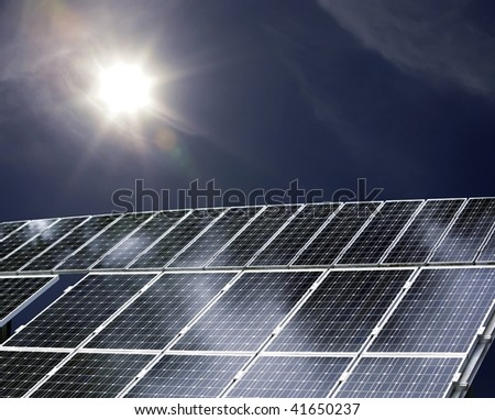 detail of a solar power plant with sun shining on it - stock photo