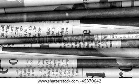 Detail of a stack of international newspapers - (16:9 black and white) - stock photo