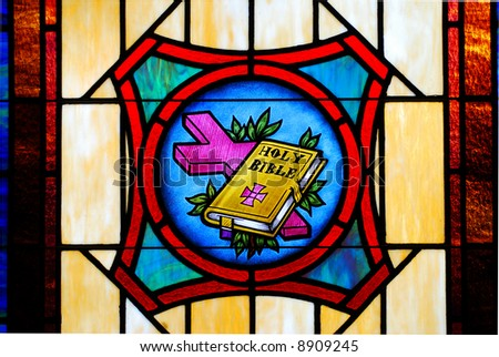 Detail of a stained glass window from a church showing a Bible and a cross - stock photo