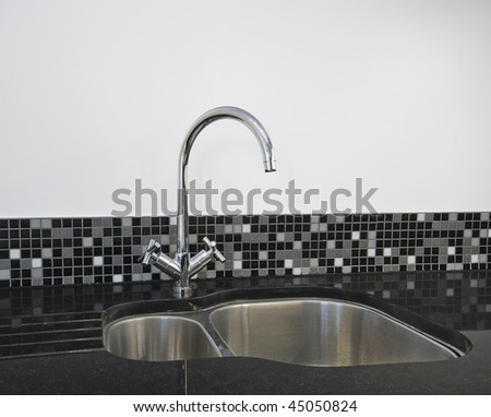 detail of a stainless steel kitchen sink on a black granite worktop - stock photo