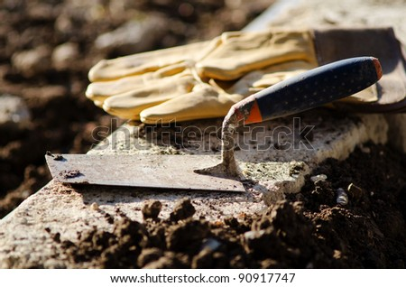 Detail of a trowel and protective gloves at the end of a workday - stock photo
