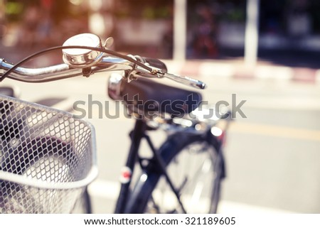 Detail of a vintage bicycle handlebar resting in the city Street - Blurred background, vintage filter effect - selective focus - stock photo