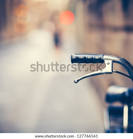 Detail of a Vintage Bicycle Handlebar Resting in the Narrow Street (vintage color toned image) - stock photo