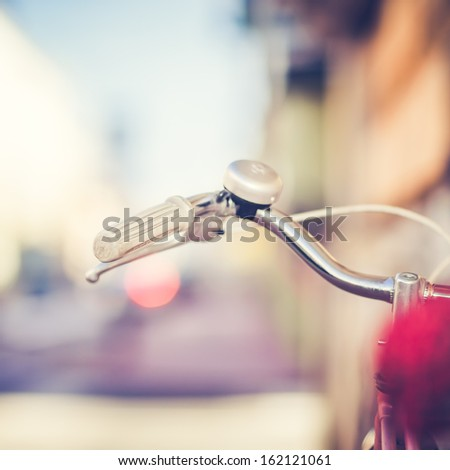 Detail of a Vintage Bike Handlebar with a Colorful Background Bokeh - stock photo