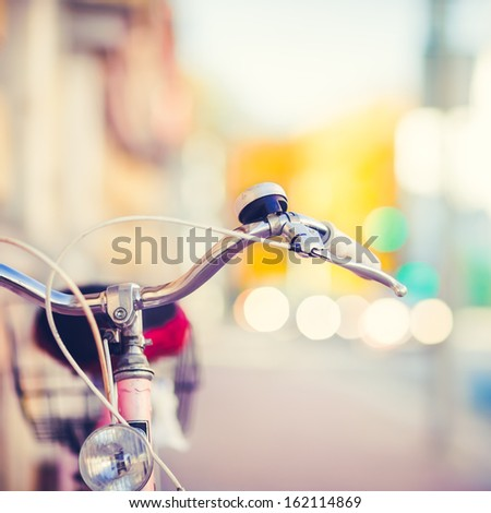 Detail of a Vintage Bike HandleBar with a Colorful Background Bokeh Made of Busy Traffic - stock photo