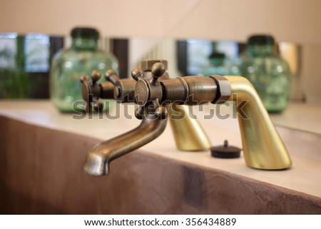 Detail of a vintage faucet placed in the bathroom of a luxury room in a country cottage hotel close to Girona, Catalonia, Spain. - stock photo