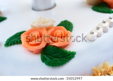 detail of a wedding cake decorated with roses, leaves, and silver - stock photo
