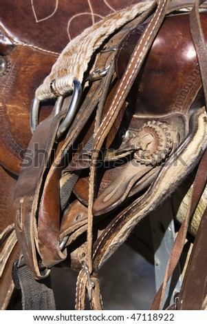 Detail of a western style horse saddle and cinch on a rail. Vertical shot. - stock photo