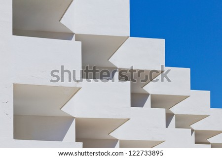 Detail of a white building in front of a blue sky - stock photo