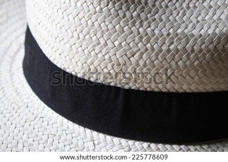 Detail of a white summer straw hat with black ribbon band - stock photo