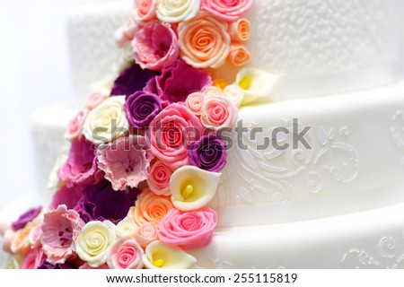 Detail of a white wedding cake decorated with pink sugar flowers - stock photo