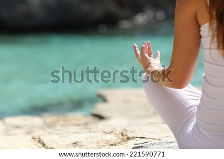Detail of a woman hand doing yoga exercises on the beach with the sea in the background - stock photo