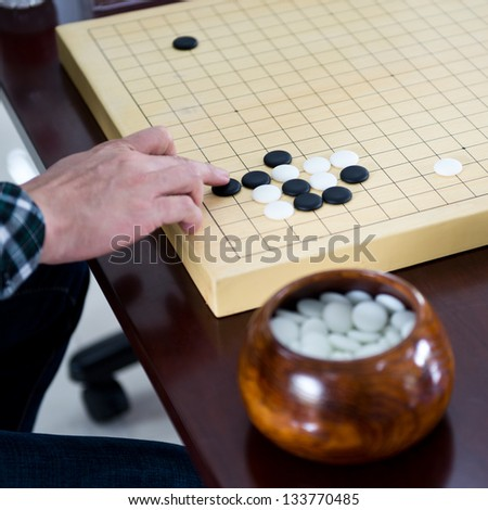 Detail of a woman playing chinese boardgame. - stock photo