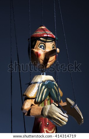 Detail of a wooden marionette of Pinocchio liar with big nose isolated on background. - stock photo