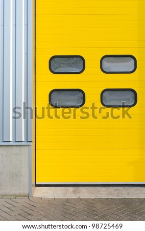 detail of a yellow industrial roller door - stock photo