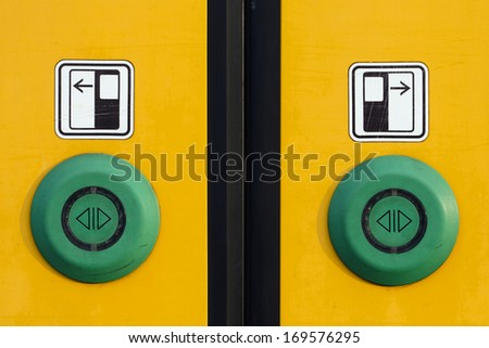 Detail of a yellow sliding door with green buttons on a modern train.  - stock photo