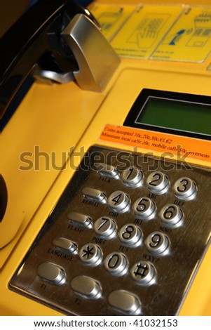 detail of a yellow telephone - stock photo