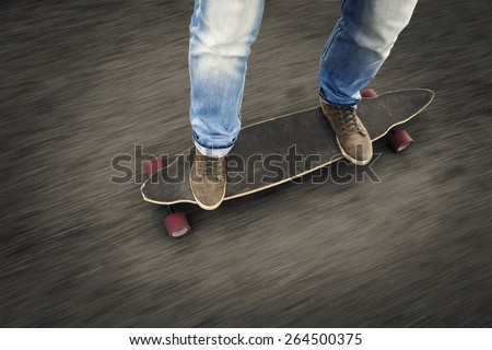 Detail of a young man feet riding a skateboard - stock photo