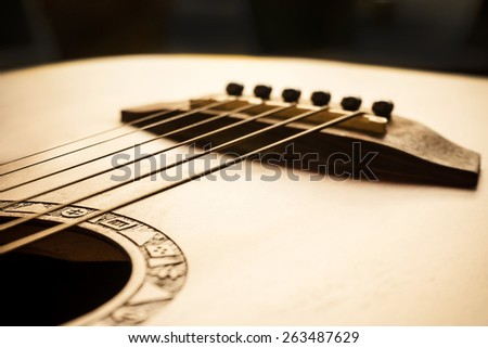 detail of acoustic guitar focus on bridge and strings, very shallow depth of field - stock photo