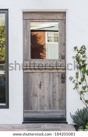 Detail of aged wooden door to a white home. An aged wooden front door of a white family home in daytime. The door has a window, reflecting the neighboring home. Also seen is porch light, and plants.