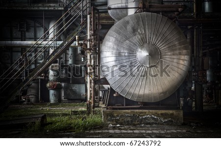 Detail of an abandoned industrial area, lots of pipelines and a big aluminum silo as eye catcher - stock photo