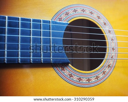 Detail of an acoustic guitar musical instrument - stock photo