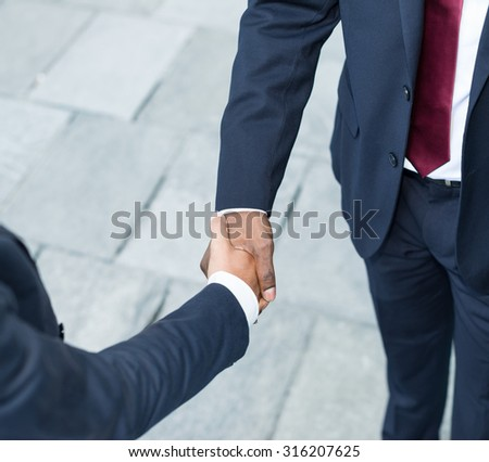 Detail of an african businessman shaking hands with a caucasian one