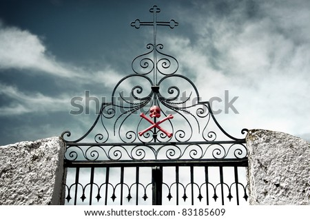 Detail of an ancient cemetery gate with a skull and crossed bones painted red - stock photo
