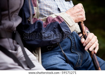 Detail of an elderly man with walking stick - stock photo