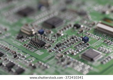 Detail of an electronic printed circuit board with many electrical components with swallow depth of field