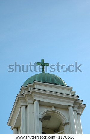 Detail of an old church building with a cross on the top. - stock photo