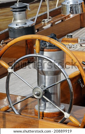 Detail of an old-fashioned boat deck with rudder, compass and other navigation tools - stock photo