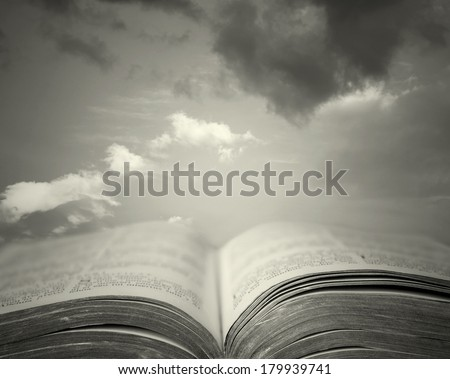 Detail of an old holy bible open with a beautiful and mystical sky in the background in black and white