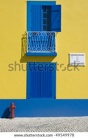 Detail of an old house facade in yellow and blue paint - stock photo