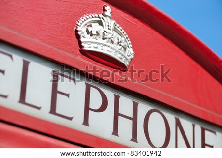Detail of an old red British Telephone Box. Focus on the crown. - stock photo