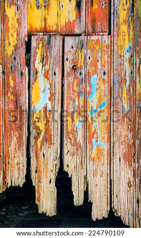 Detail of an old wooden door with peeling paint and rusty nails - stock photo