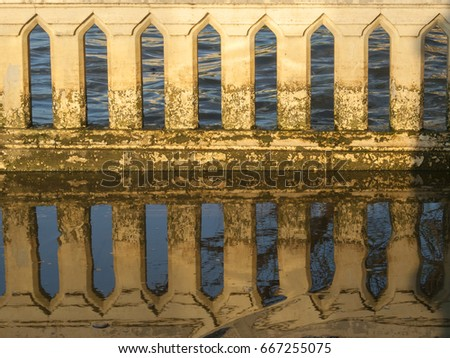 Detail of an ornate concrete wall at dusk with pillars is reflected in the water, Bangkok, Thailand