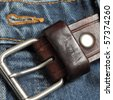 Detail of an unbuckled leather belt on a faded pair of blue jeans - stock photo
