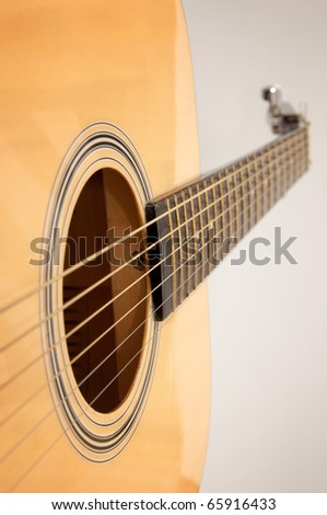 Detail of an yellow, wooden acoustic guitar over a white background