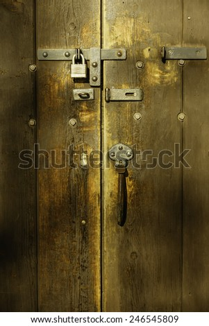 Detail of antique wooden door with padlock and hardware on restored Victorian house built in 1858 and now maintained as a public museum - stock photo