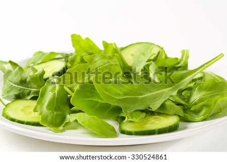detail of arugula leaves and sliced cucumber on white plate