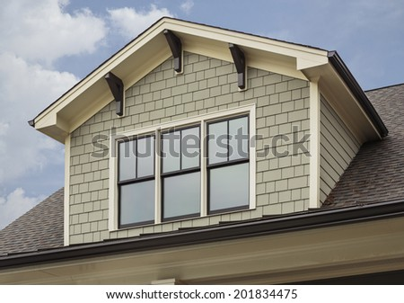 Detail of attic of green family home on a sunny day. House has shingles and siding, with white and brown house detail. - stock photo