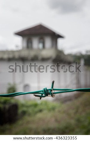 Detail of barbed wire on the background of a prison guard tower. Fence of barbed wire at the prison.  - stock photo