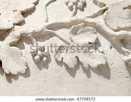 detail of bas-relief over stone showing grapevine leafs an fruits - stock photo
