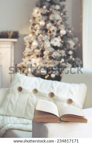 Detail of beautiful holdiay decorated room with Christmas tree and white comfortable chair with soft knitted blanket and cushion on it, reading time - stock photo