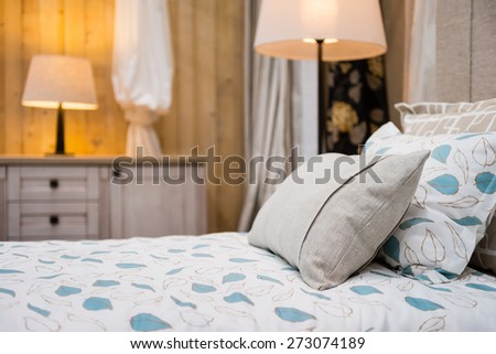 Detail of beige pillow on the bed with two lamps in the background - stock photo